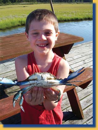 An image of a boy with a crab on the Inn's private dock